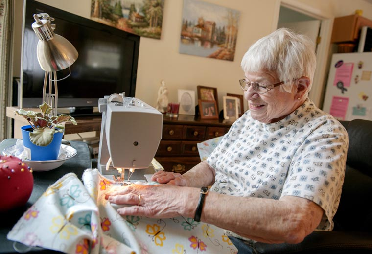 Elderly woman works on sewing machine