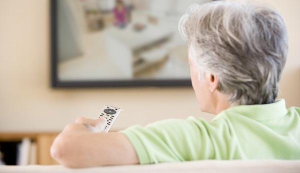 Senior man watching TV while wearing a green shirt